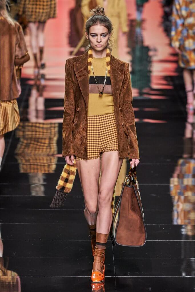 Sfilata Fendi Roma, modella con abiti color marrone e giallo